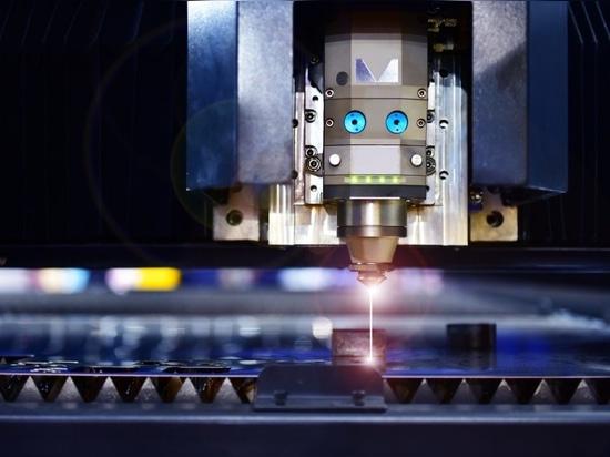 Machine industrielle de découpe au laser en découpant la tôle à l'aide d'une lampe à étincelles.